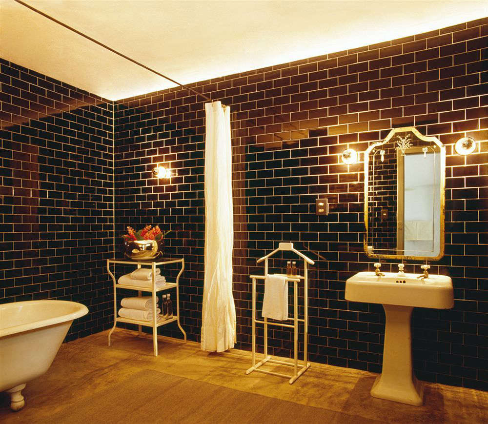 A bath off one of the farmhouse bedrooms with glossy black subway tile and retro bath fixtures.