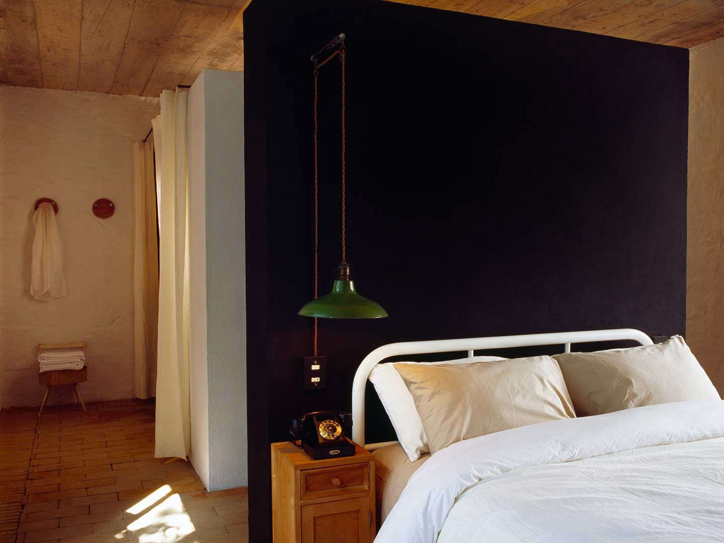 One of the 3 smaller bedrooms in the original farmhouse with a matte black wall and antique lighting.