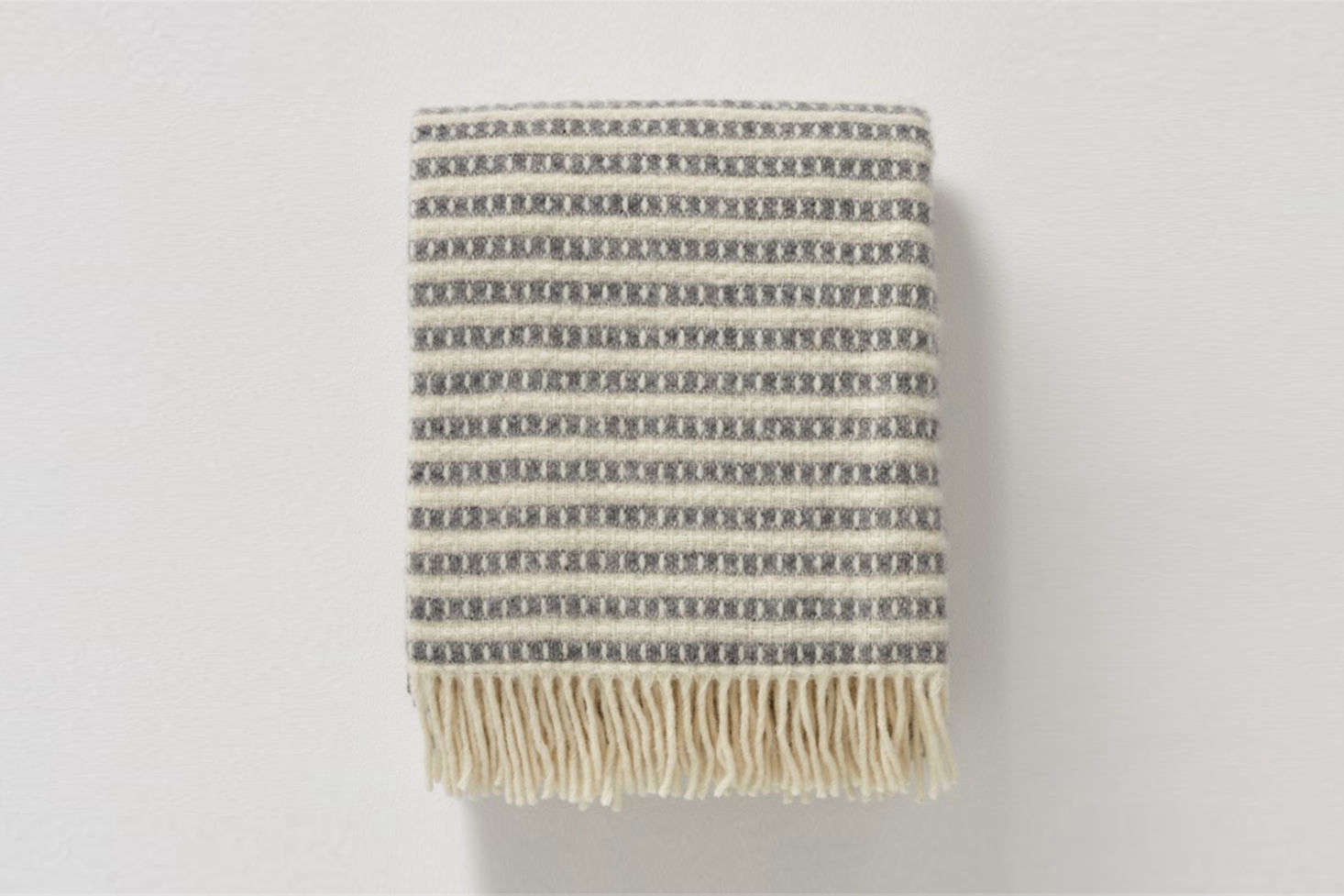 The Olle Wool Blanket in Pale Grey Ecru is $0 at Toast in the UK.