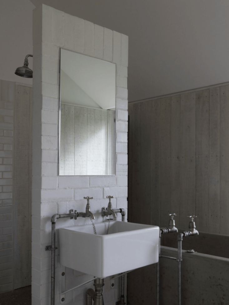 A Stable Reborn in Rural Norfolk In the bath, Kohn left the plumbing exposed.
