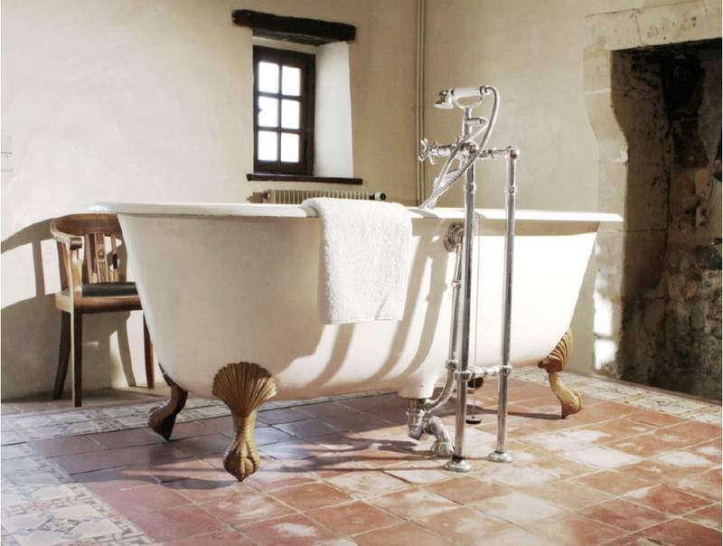 A roomy bathroom with a clawfoot tub and old tile floor.