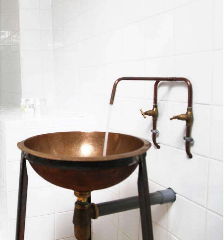 A deconstructed bath with a DIY copper faucet and sink.