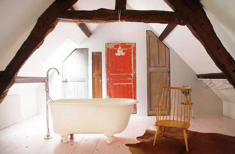 A quirky attic bath designed with four antique doors of different proportions.