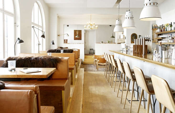Leather upholstered benches and brown sheepskin mingle with industrial lights.