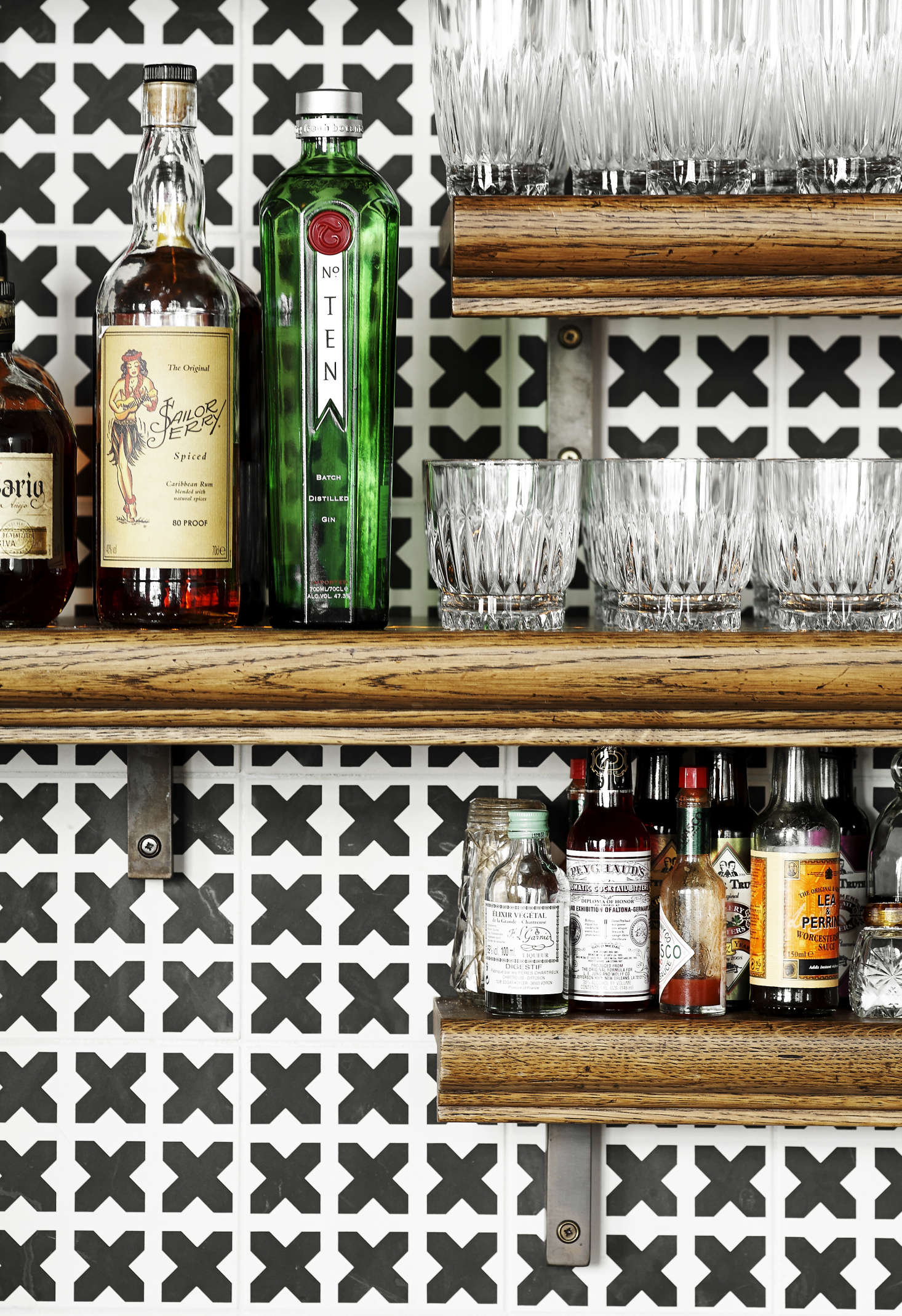 The bar backdrop is tiled in a black-cross pattern.