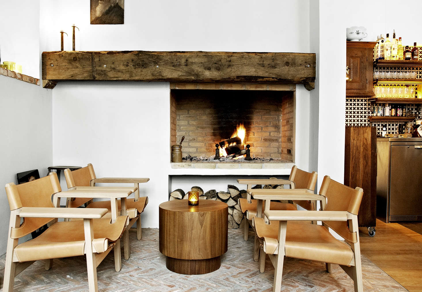 The bar opens to blazing fire in a beamed hearth. (Note the inset stacked firewood.) Danish designerBørge Mogensen&#8