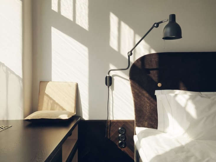 Miss Clara Glamorous Lodgings in a Former Girls School in Stockholm A sculptural &#8\2\20;type objet&#8\2\2\1; Lampe Gras lampis wall mounted as a bedside lamp.Note the dark wood herringbone wainscot.