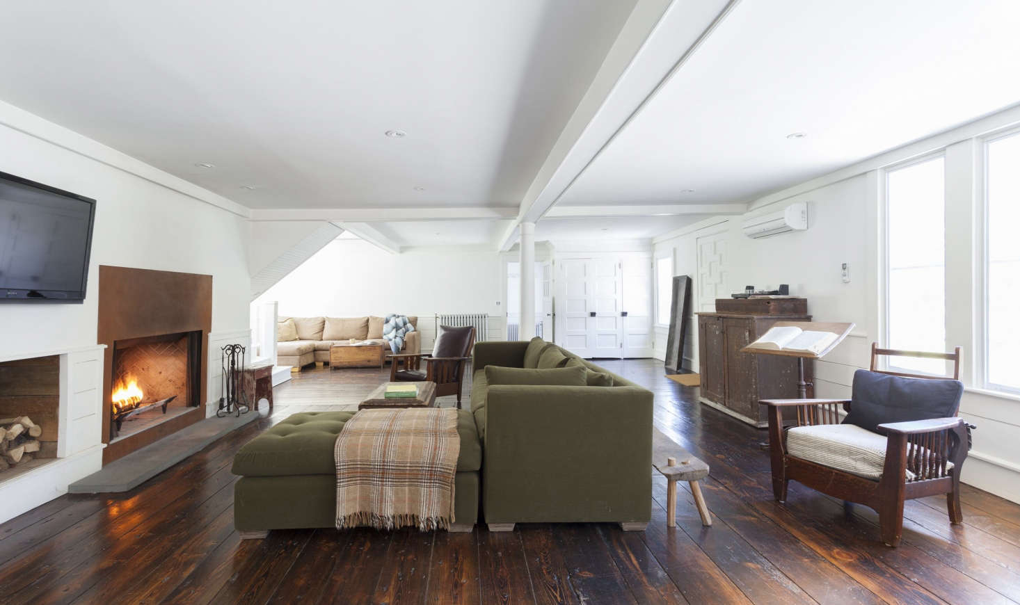 The open-plan living room/family room/dining room has its own steel-front fireplace and original wide-plank floors. The wainscoting and ceiling coffers were built from pine trees felled and milled on the property. The living room is painted in Benjamin Moore&#8
