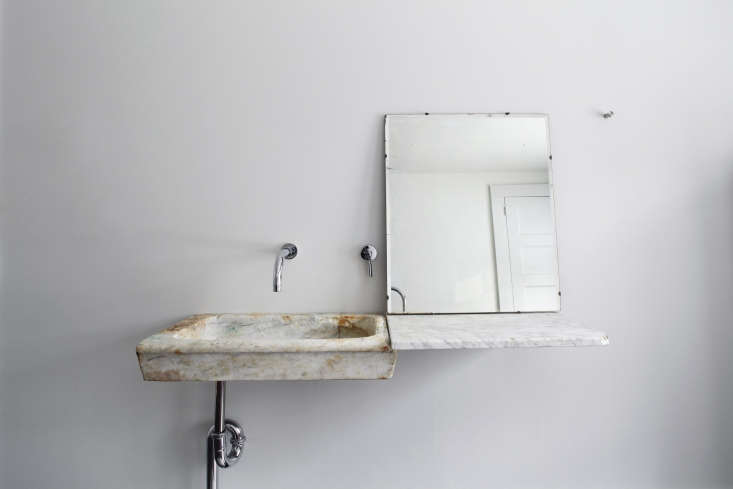 A workaround for a bathroom counter fully clad in marble: a small slab anchored to the wall forms a deconstructed vanity, as seen inThe Country Rental: A Floating Farmhouse in Upstate New York.