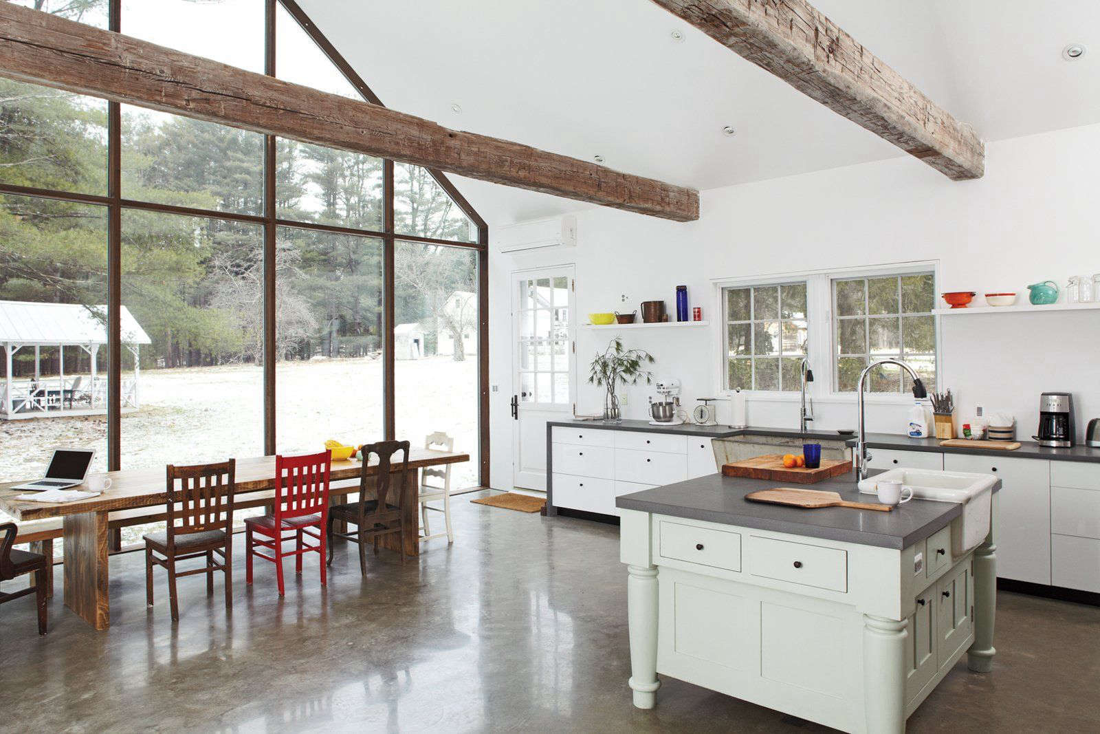 The kitchen layout is based on the original footprint of the two demolished shelters. The glass steel window frame mirrors the lines of the original farmhouse windows. The beams, salvaged from a 0-year-old barn in Pennsylvania, were engineered to work with the steel window frame and skyscraper glass.