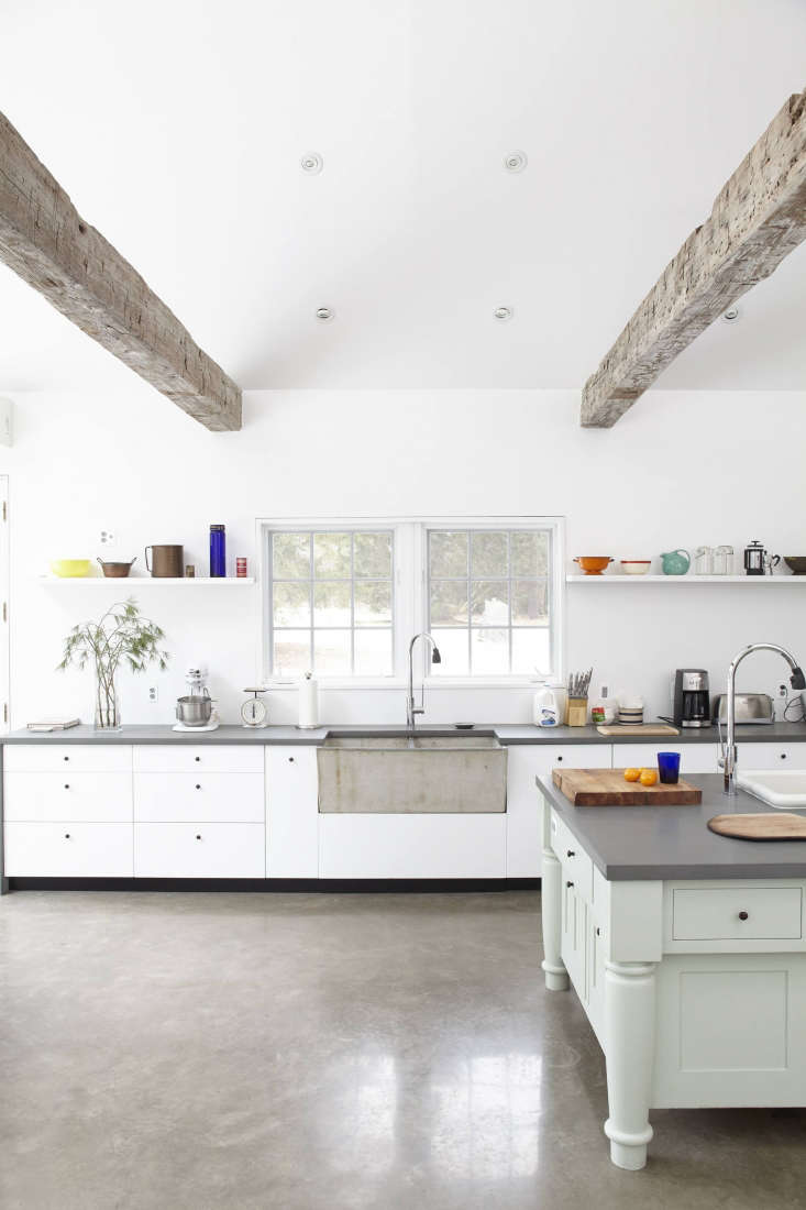 For the kitchen of the Floating Farmhouse, Givone salvaged ceiling beams from a 0-year-old barn in Pennsylvania and found the concrete sink in the basement of a neighboring farmhouse.