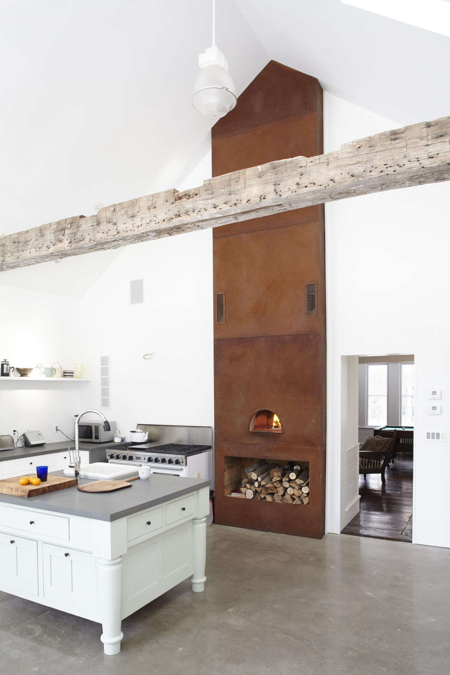 The kitchen has a wood-fired pizza oven faced with oxidized Corten steel. For more on the details of the kitchen see our postSteal This Look: The Ultimate Farmhouse Kitchen.