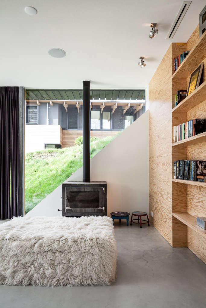 a woodstove provides a hearth for the living area. the diagonal wall behind it  15