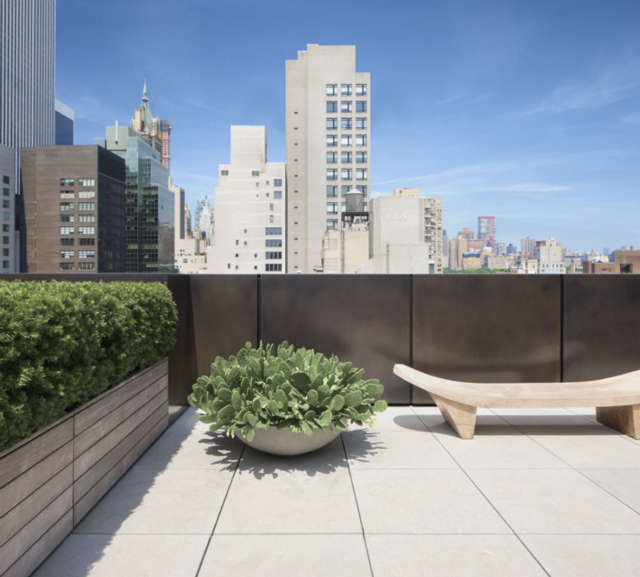 Park Avenue Roofscape: PARK AVENUE ROOFSCAPEJCAs design for this previously unfinished ,800 s.f. roof creates a private oasis by concealing existing elements that create visual chaos and simplifying sight lines to bring the skyline view to the forefront. Machine room walls are screened with resin panels. Bent sheets of bronze conceal the parapet from view. An aluminum and wood shade canopy cantilevers off the buildings side. And the greenery in wood cladded planters softens the rigid geometry of the space,