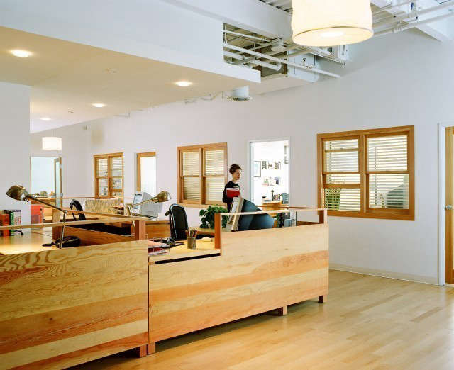 Film Production Office, Santa Monica: This is the general office area for a film production company. My client wanted the office to have an old Soho loft character, raw, and unpretentious. I chose construction quality Douglas Fir for the desks to help create that character. The grain of the wood was used as a decorative element. The interior windows bring light into the central office, and the wood frames echo the material of the desks. I used rice paper pendant lamps from IKEA throughout, giving a warm glow and a casual appeal. Photo: Dominique Vorillon