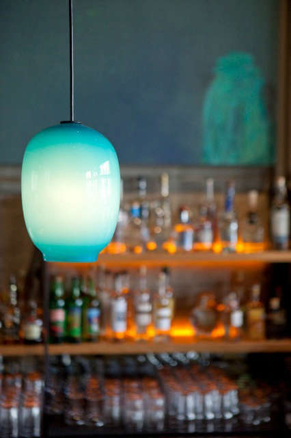 Bar Pendants: Custom turquoise blue glass pendants are by local glass blower Lee Miltier. The simple raw steel and wood back bar features amber LED lights which graze the surface of the concrete walls. Photo: Eurydice Galka