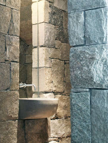 powder room: a custom concrete sink cantilevered from a stone niche