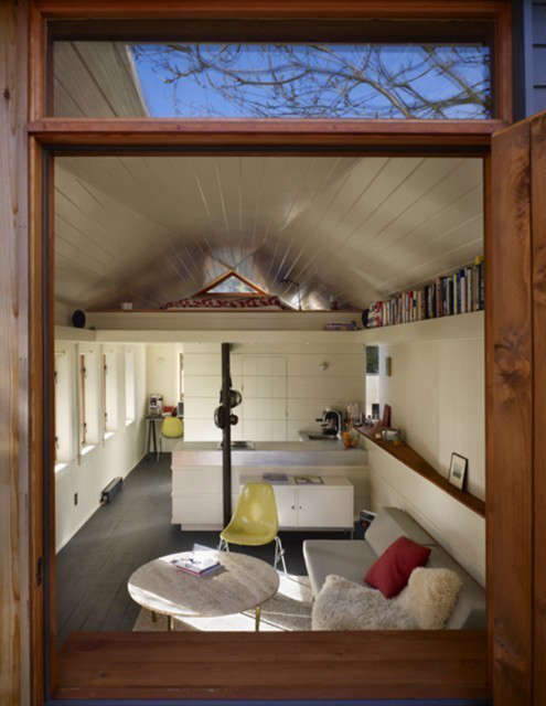 Garage Conversion: 3-square-foot garage conversion features a faceted ceiling to guide warm air to the triangular vent window for passive ventilation. Space-saving strategies used throughout: a support beam functions as a kitchen pot rack, and a bookshelf is tucked in the interior eaves. Photo: Ben Benschneider