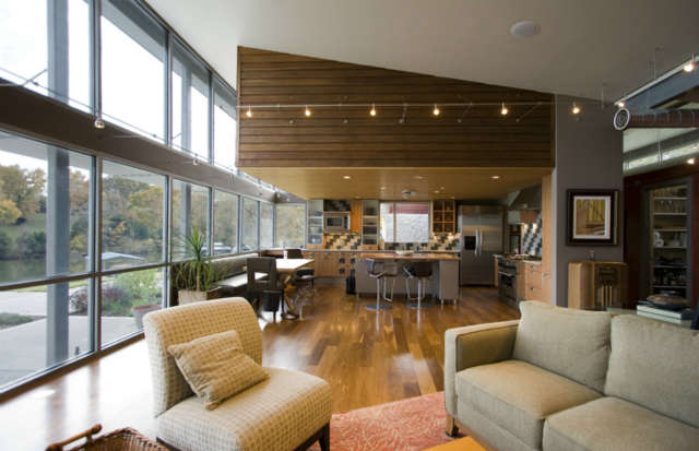 Lake House Remodel: Staying within the footprint of a tear-down ranch style house, the new home was given a modern appreciation for lakeside views with commercially scaled storefront windows, steel beam and posts, and a brise soleil to filter daylight into the living spaces.