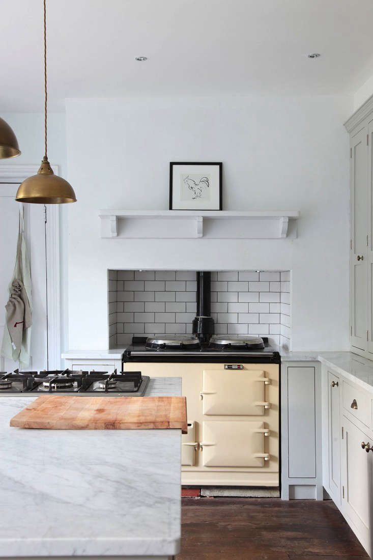 AMinimalist English Kitchenis outfitted with a traditional Aga range (and an extra cooktop, located on the island).