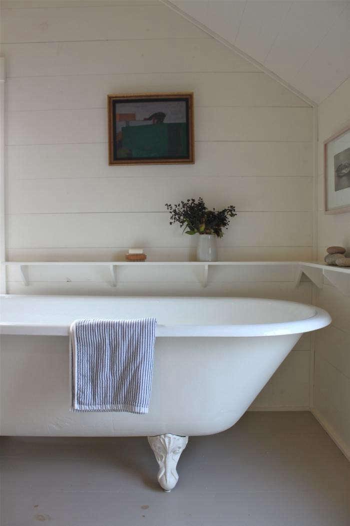 A Cottage Reborn in Coastal Mainehas hardwearing bathroom floors in a light gray.