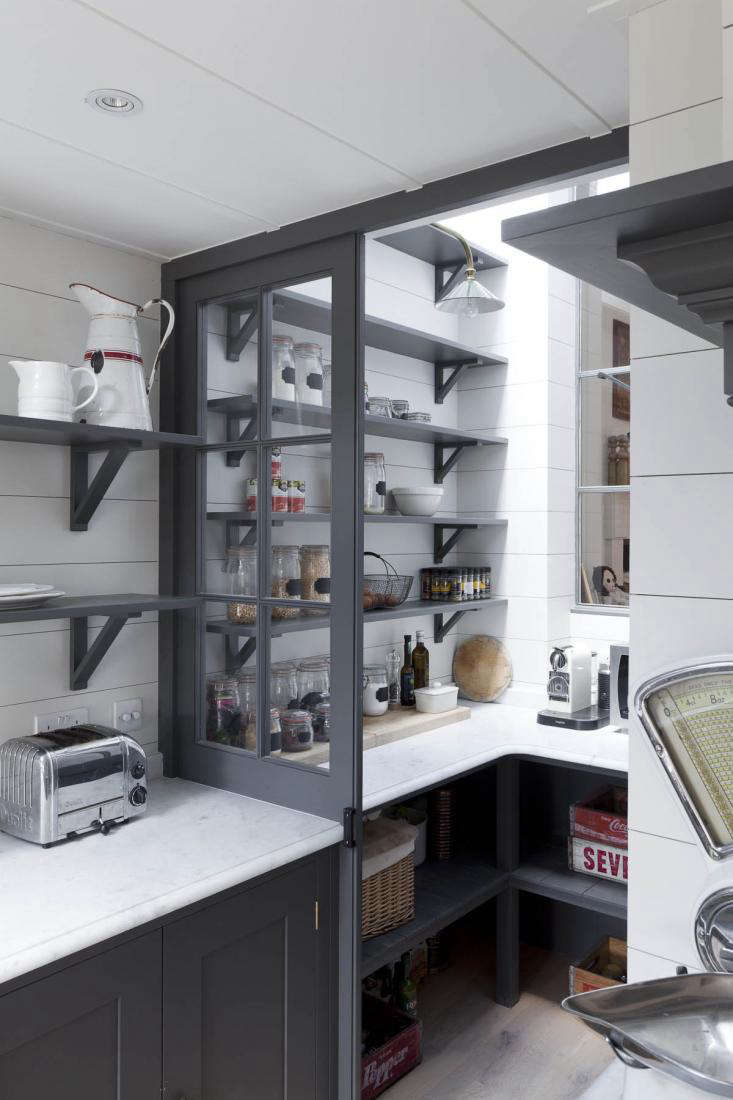 """Says photographer Abi Campbell of her kitchen pantry, """"I had a funny dead space at the end of my kitchen, and Plain English suggested that I turn it into a pantry. I blew my budget here, but I love being able to see everything and getting my hands on it fast."""" See the rest of the gray-and-white design in Reader Rehab: A Photographer's Kitchen in London. Photograph by Matt Clayton, courtesy of Abi Campbell."""