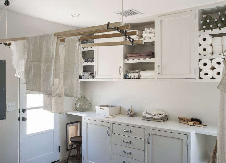 The über-organized laundry room: ASheila Maiddrying rack, suspended from the ceiling, frees up floor space and a canvas basketcorrals supplies. SeeRehab Diary: Amanda Pays and Corbin Bernsen Air Their Dirty Laundry.