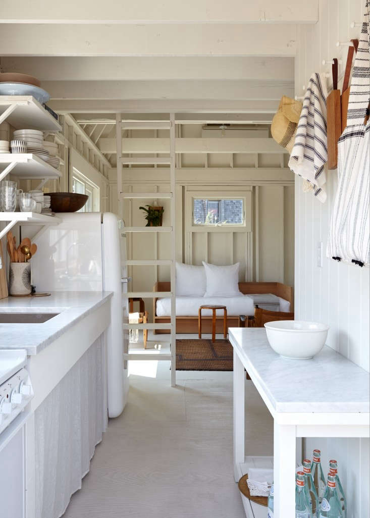 A minimalist white sink skirt conceals storage space in this airy Fire Island beach house owned byAnn Stephenson and Lori Scacco. PhotographbyKate Sears, fromBookmark for Next Summer: 7 Storage Ideas to Steal from a High/Low Beach Shack.