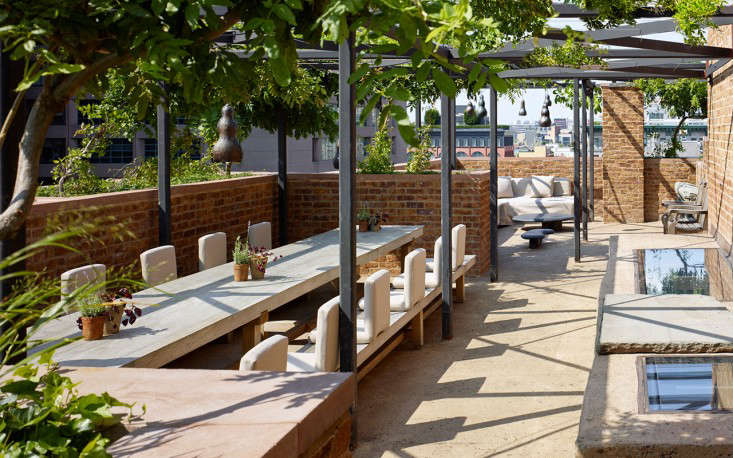 On the roof terrace, multiple seating and dining areas sit beneath wisteria-wrapped pergolas.