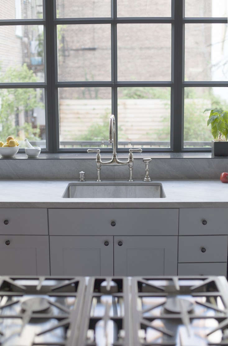 A classic bridge faucet paired with a stainless sink overlooks the garden.