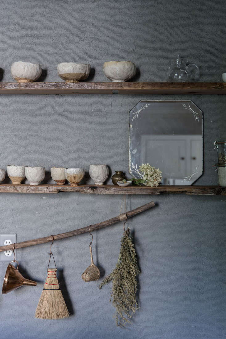 A charming hand broom hangs among kitchen tools and drying herbs in a kitchen. See more inThe One-Month Makeover: Beth Kirby&#8