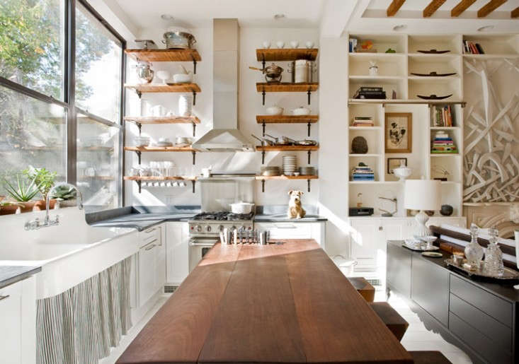 The Brooklyn Home Companycreated an L-shaped country kitchen with a long wood table and open shelving in a Brooklyn townhouse apartment.