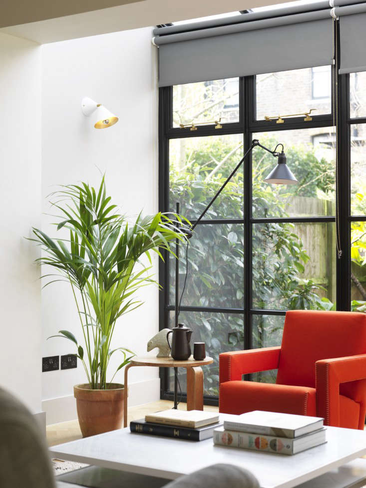 Double roller shades are used to cover a wall of windows: During the day, sheer shades filter and diffuse the light coming in, while blackout shades keep the room dark at night. Photograph featured in A 600-Square-Foot North London Renovation Blessed with the Mellersh Touch. Photograph by Chris Tubbs.