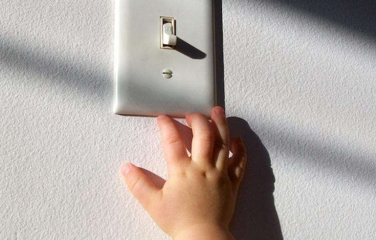 Child reaching for light switch