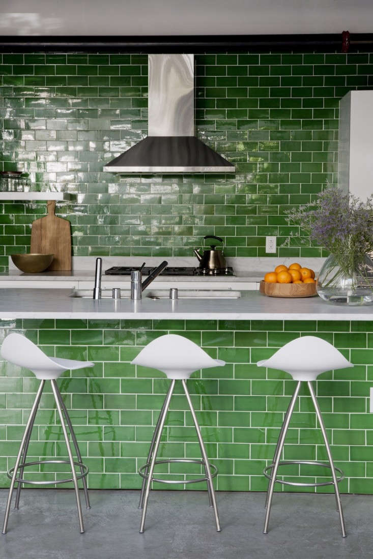 In a kitchen revamp by DISC Interiors, green tiling under the counter creates the illusion of floor-to-ceiling tile. See more inAn LA Kitchen Goes Green.