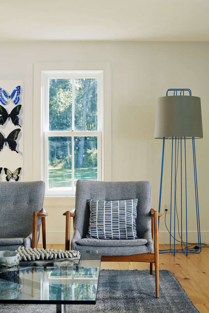 Dunja countered the potential coldness of the chrome and leather with a pair of Danish armchairs found on Etsy. The pillow is one of her own designs in a pattern called Brick. The towering light is Blu Dot&#8