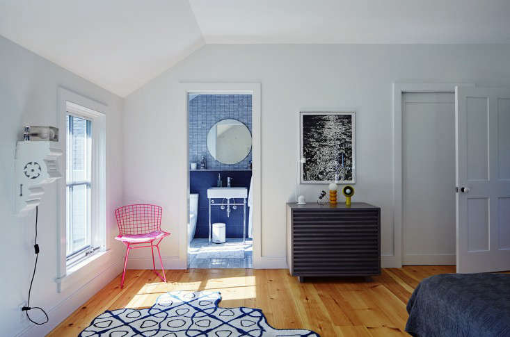 Another pink Bertoia chair appears in the master bedroom. A Leslie Parke painting of water hangs over a collection of vintage lights. The rug is Gandia Blascoe&#8