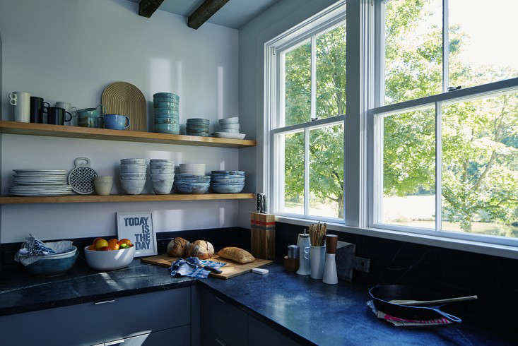 A long-ago kitchen fire led Dunja to gut what was there. The new setup has open shelves, soapstone counters, and custom cabinets. The ceramics are by Bennington Potters, a reminder of her childhood kitchen, and Dunja&#8