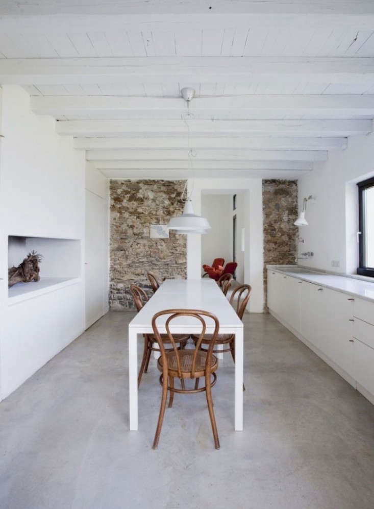 Minimalist built-ins and a polished concrete floor meet an old stone wall inA Whitewashed ItalianFarmhouse with Just a Dash of Colorby A