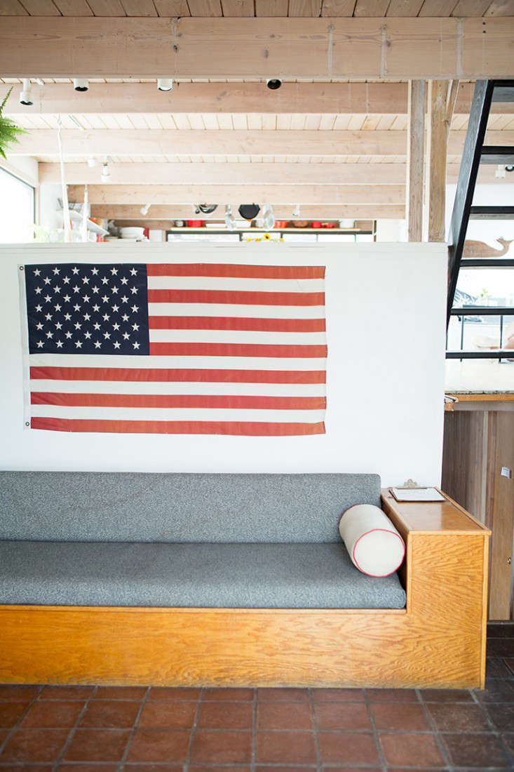 An American flag displayed above a built-in sofa on the houseboat of Fredericks & Mae team Gabe Cohen and Jolie Signorile. Photograph by Douglas Lyle Thompson fromRehab Diary: The Ultimate Houseboat in NYC.