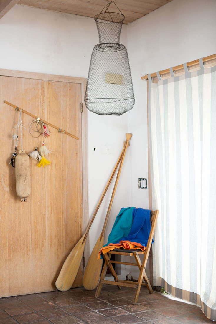 Rehab Diary The Ultimate Houseboat in NYC A curtained sliding glass door leads to the entry hung with a fishing trap. That&#8\2\17;s one of Todd Heim&#8\2\17;s linen towels on the chair. (See our post on the Summer&#8\2\17;s Best Beach Towels for a better look and more examples.)