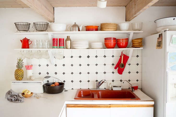 Rehab Diary The Ultimate Houseboat in NYC The boat came with a burnt orange sink, so the group kitted out the kitchen with orange and white tableware.