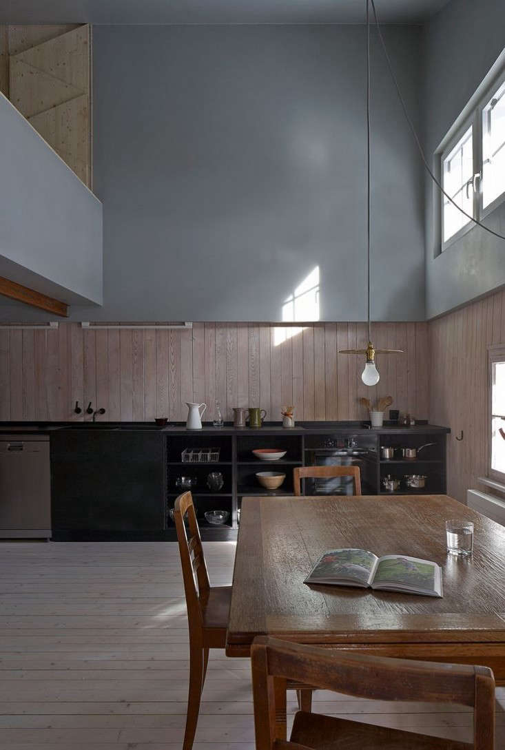 The heart of the house is a double-height kitchen and living area. Whitened wood paneling and flooring contrasts with the dark, custom-built kitchen and gray plastered walls.