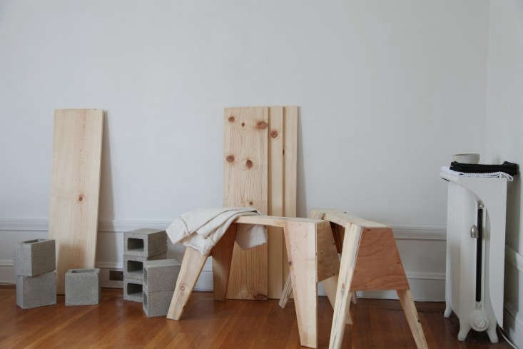 The original flat-pack furniture: everything you need to make a sawhorse dining table (plus cinderblocks and extra boards, if you need extra seating, too). Photograph from The Sawhorse Holiday Table for Less than $0.