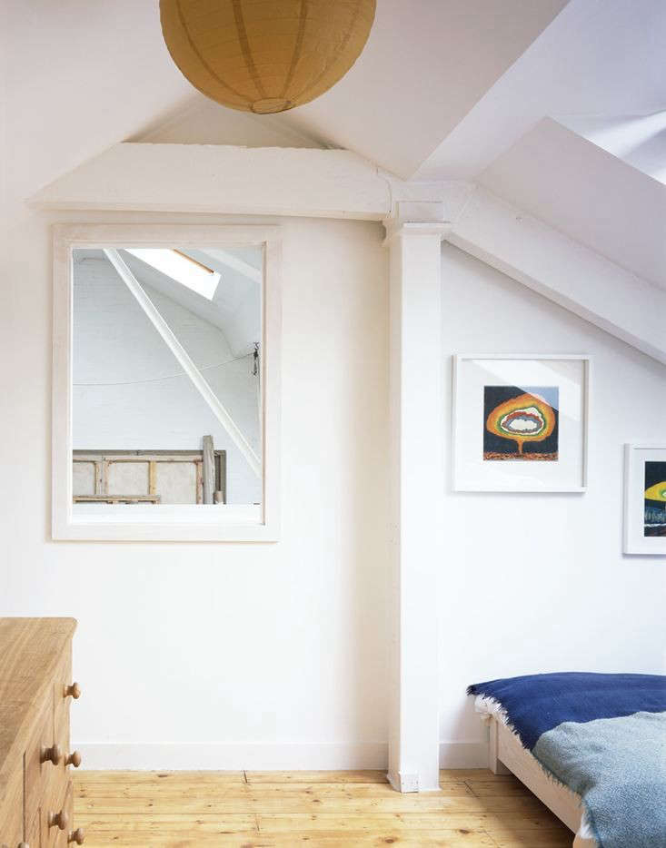 One of the two bedrooms upstairs; each room with a window that opens out onto paintings in progress.