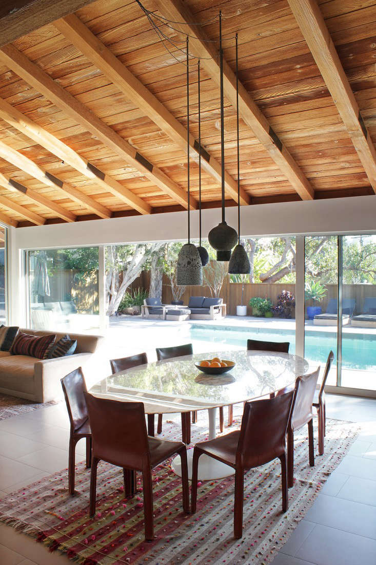 This is LA: The open living room/dining room overlooks the pool. Adam Silverman ceramic pendant lights were previously hung throughout the space; to create a focal point, Todd clustered them over the Saarinen dining table.