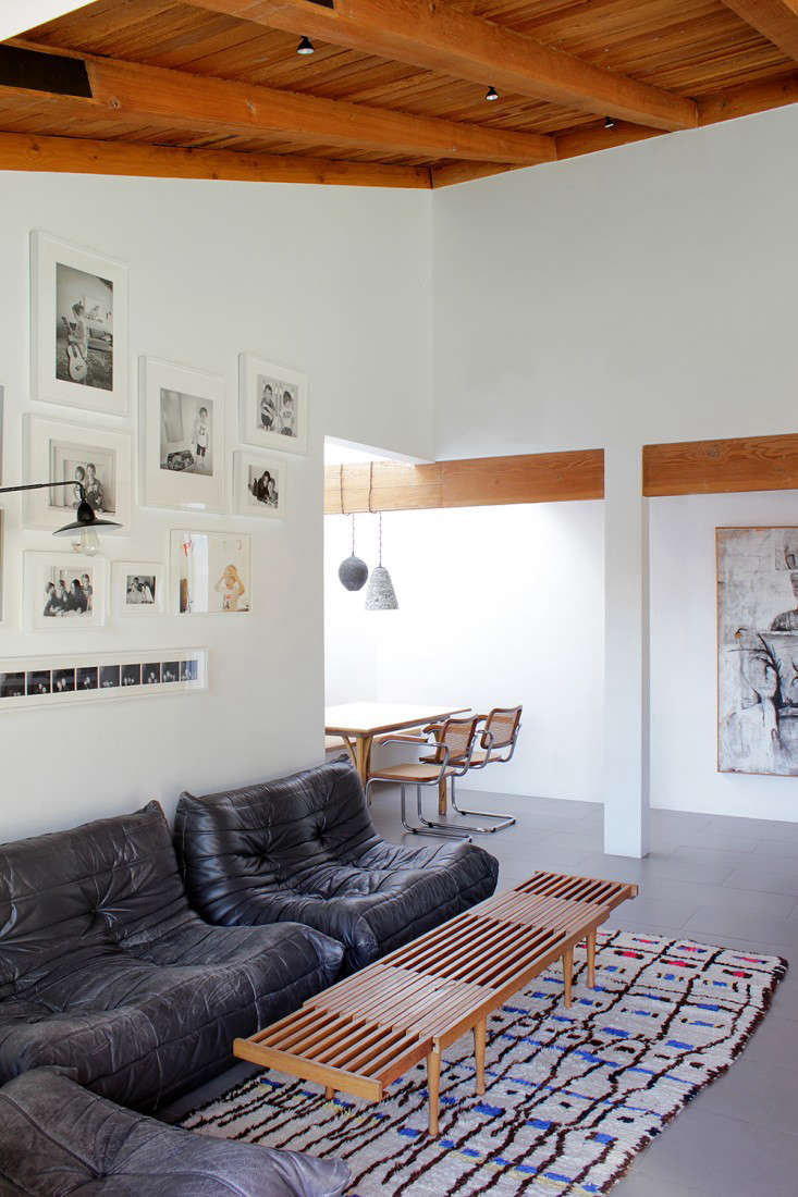 In the family room, white-framed family photos hang over vintage leather Togos sofas designed by Michel Ducaroy for Ligne Roset. The vintage Moroccan rug is from Woven Accentsof West Hollywood.