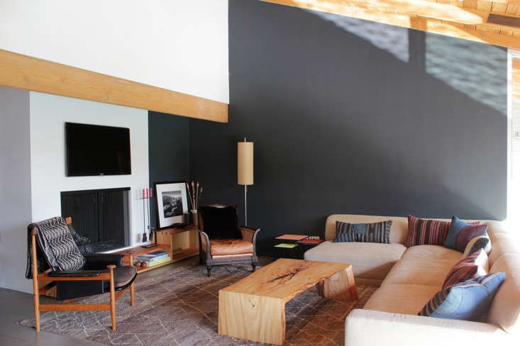 The living area is set off by a gray-painted wall and sofa custom designed by Nickey Kehoe. To connect the fireplace with the room, Todd inserted a two-tiered ledge/bookshelf made of Douglas fir.