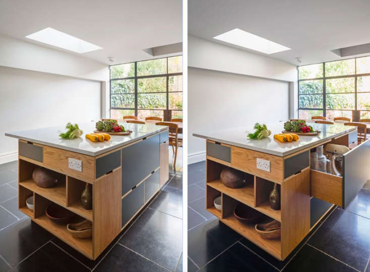 Above, L and R: Each side of the island offers customized storage: The front (shown here) displays large serving pieces; the table end has flatware drawers, the side closest to the kitchen counter is stocked with bins for pots and pans, and the opposite side holds occasionally used items. Note the skylight at the back of the room that gives an extra influx of sunlight. Photographs by Jocelyn Low from Uncommon Projects.