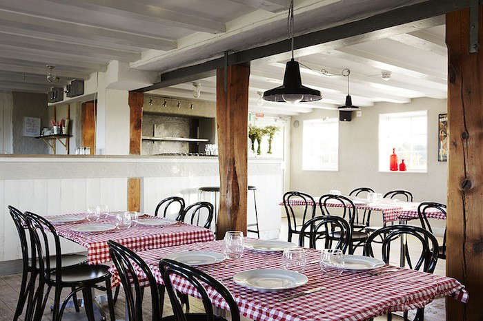 The red and white checkered table clothes add a warm note to the rustic restaurant area.